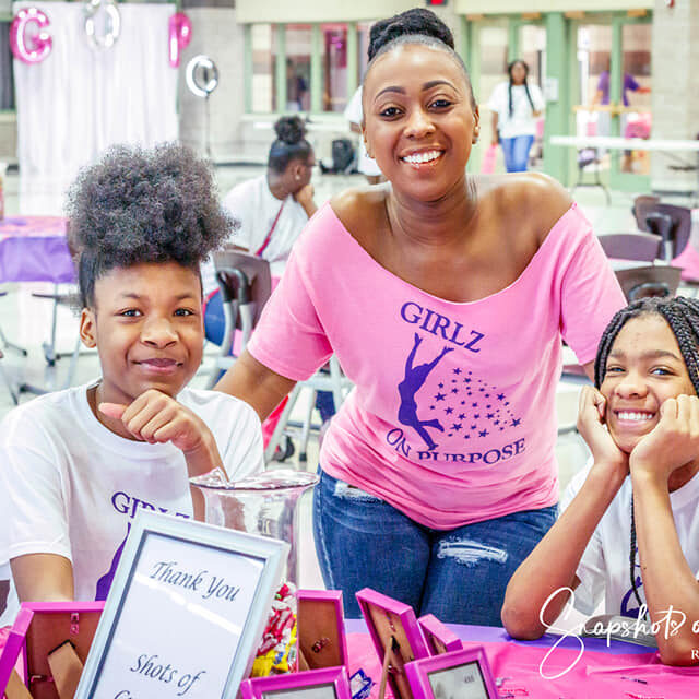 A woman stands behind sitting two girls; they are all smiling at the Girlz on Purpose Event